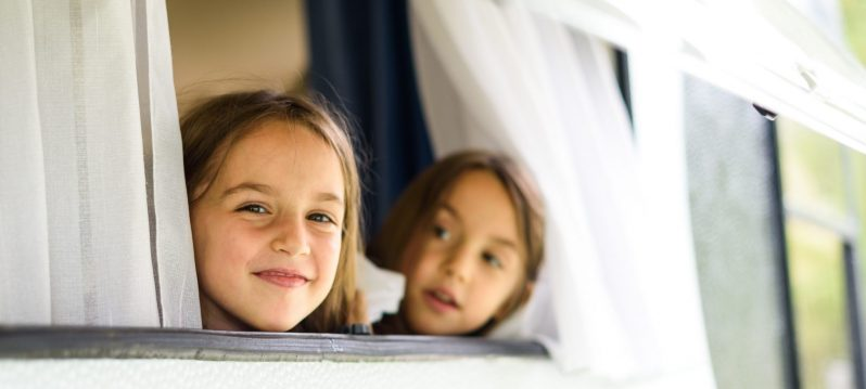 Children are looking through caravan or camper motorhome window. Twin sisters are enjoying vacation, travelling and camping, looking through old camper caravan window.